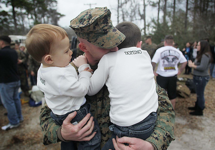 Staff Sgt. Mike Domino hugs his sons, one-year-old, Jack and five-year-old, Joey after returning to Camp Lejeune, 02/04/ 2012. 270 Marines and sailors with Battalion Landing Team, 2nd Battalion, 2nd Marine Regiment and approx 30 Marines and sailors with Combat Logistics Battalion 22 returned to Camp Lejeune Saturday Afternoon. (AP Photo, The Daily News, Chuck Beckley)