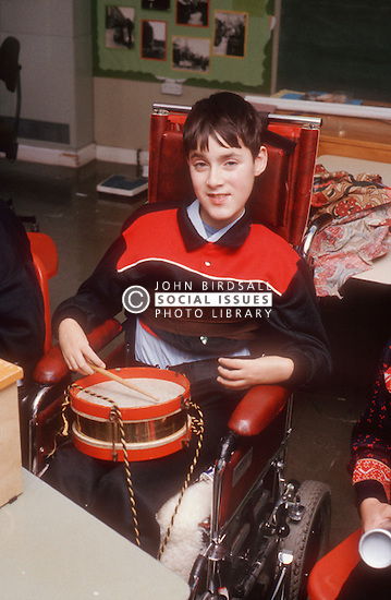 Young boy with disability; who is wheelchair user; playing drum in school music lesson,