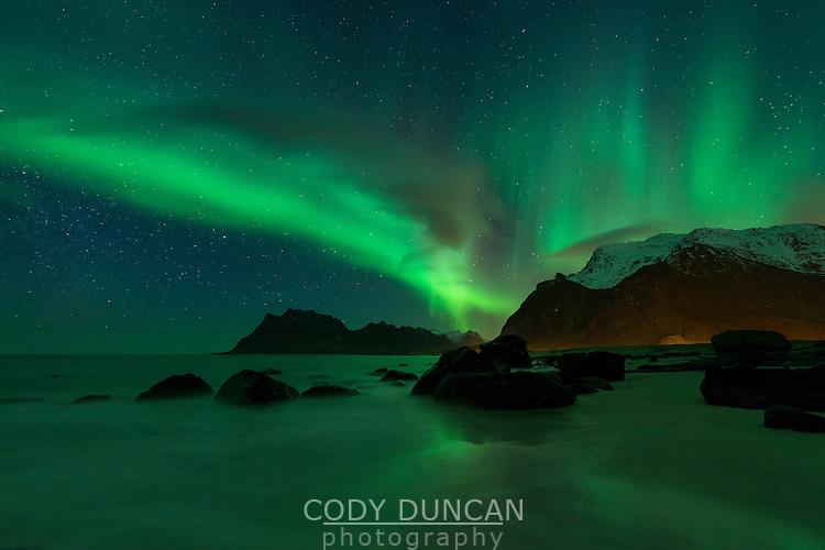 Northern Lights - Aurora Borealis shine in Sky over Uttakleiv beach, Vestvågøy, Lofoten Islands, Norway