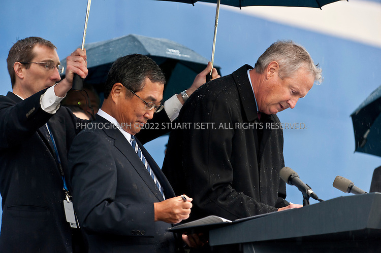 9/26/2011--Everett, WA, USA..Jim Albaugh, president and chief executive officer of Boeing Commercial Airplanes (right) and ANA President Shinichiro Ito (left) sign documents officially handing over Boeing's first 787 Dreamliner...Thousands of Boeing employees gathered in the rain to celebrate the delivery of the first 787 Dreamliner to launch customer ANA (All Nippon Airways) from Japan. The fuel efficient composite aircraft was towed to the front of the huge factory doors where it was assembled, and presented to ANA President Shinichiro Ito in front of thousands of invited dignitaries and Boeing workers. The first 787 was supposed to be delivered 3 years ago but despite delays Boeing still has orders for over 800 of the planes...©2011 Stuart Isett. All rights reserved.