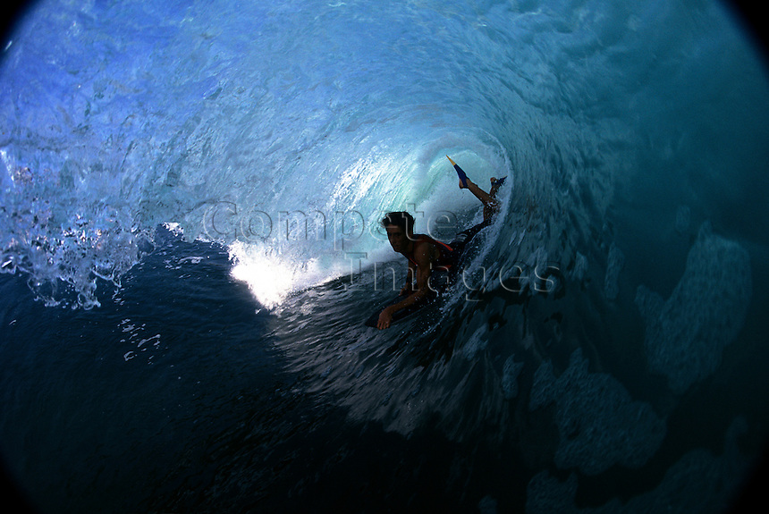 Body boarder riding through a pipeline wave