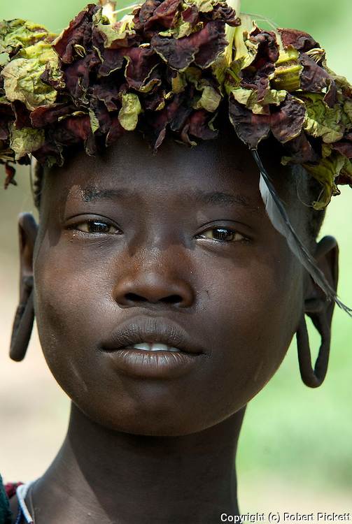 Young Girl with flower head gear, Mursi Tribe, Mago National Park, Lower Omo Valley, Ethiopia, portrait, person, one, tribes, tribal, indigenous, peoples, Southern, ethnic, rural, local, traditional, culture, primitive,.Africa....