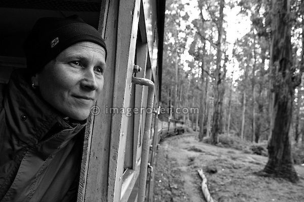 Western female tourist on the Nilgiri Mountain Railway between Coonoor and Ooty. India, Tamil Nadu 2005. --- Info: The Nilgiri Mountain Railway (NMR) is the only rack railway in India and connects the town of Mettupalayam with the hill station of Udagamandalam (Ooty), in the Nilgiri Hills of southern India. The construction of the 46km long meter-gauge singletrack railway in Tamil Nadu State was first proposed in 1854, but due to the difficulty of the mountainous location, the work only started in 1891 and was completed in 1908. This railway, scaling an elevation of 326m to 2,203m and still in use today, represented the latest technology of the time. In July 2005, UNESCO added the NMR as an extension to the World Heritage Site of Darjeeling Himalayan Railway.