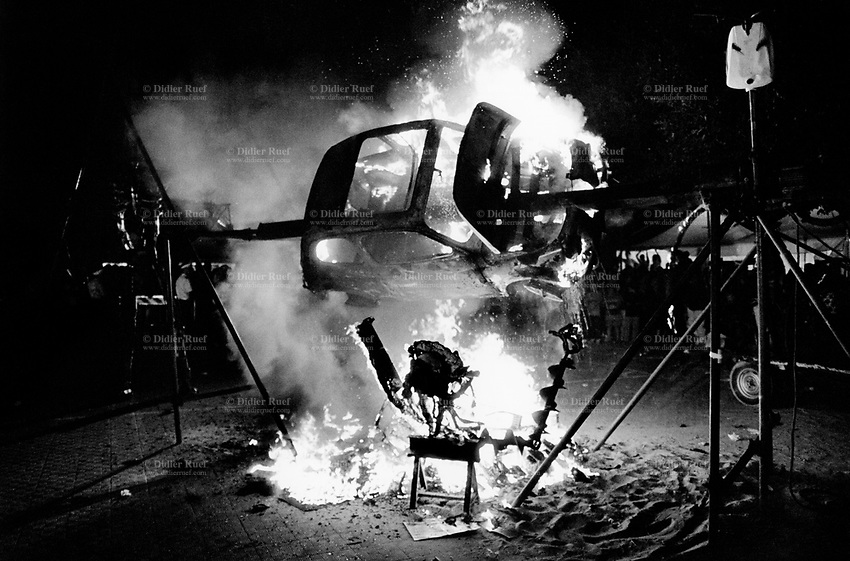 "Italy. Province of Sicily. Menfi. Mutoid Waste Company.  A Fiat 500 is burned on a giant barbecue at ""Inycon"" festival. Using all types of industrial scrap for their raw materials the Mutoid Waste Company are a mobile and adaptable group of performance artists. Having the necessary equipment to allow them complete freedom, they have created an entirely new form of scultural-musical performance crossing the boundaries of circus, theatre and art. © 1999 Didier Ruef"