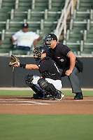 Kannapolis Intimidators catcher Ryan Plourde (28) sets a target as home plate umpire Alex Trujillo looks on prior to the start of the game against the Lakewood BlueClaws at Intimidators Stadium on July 16, 2015 in Kannapolis, North Carolina.  The BlueClaws defeated the Intimidators 3-1.  (Brian Westerholt/Four Seam Images)