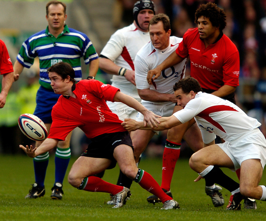 Photo: Richard Lane..England  v Wales. RBS Six Nations Championship. 20/03/2004..Shane Williams gets the ball away as Olly Barkley tackles.