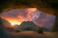 The view through a small alcove at a blazing sunset over the sandstone formations of Vermillion Cliffs wilderness.