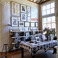 An alcove in the barn with bookshelves and a table is used as a study area