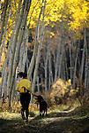 A young woman and her dog run  through an aspen grove near Jackson Hole, Wyoming.