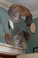 A collection of hats hangs on a pair of antlers in the entrance hall