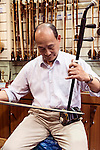 Music store owner in Shanghai, China plays Erhu Chinese fiddle