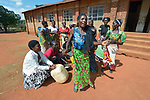 Women sing and dance outside a church after they concluded a meeting of guardian for orphans and vulnerable children in Emanyeleni, Malawi. With assistance from the AIDS program of the Livingstonia Synod of the Church of Central Africa Presbyterian, the guardians have been trained to provide nutritious food, keep children in school, and reduce problems of stigma and discrimination.