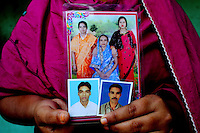 21 year old Nelufa Begum holds pictures of her father, mother, brother and sister-in-law, all of whom died in the blaze. She has not been able to find and identify the bodies. At least 112 people died, and more than 100 were injured at a fire at the Tazreen Fashions textile factory in Dhaka. Bangladesh's garment industry has a notoriously bad fire safety record; if the right precautions had been taken, the fire could have been prevented.
