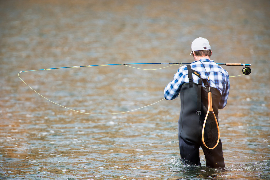 An angler ties on a new fly while fishing the Madison River in Bear Trap Canyon west of Bozeman, Montana.