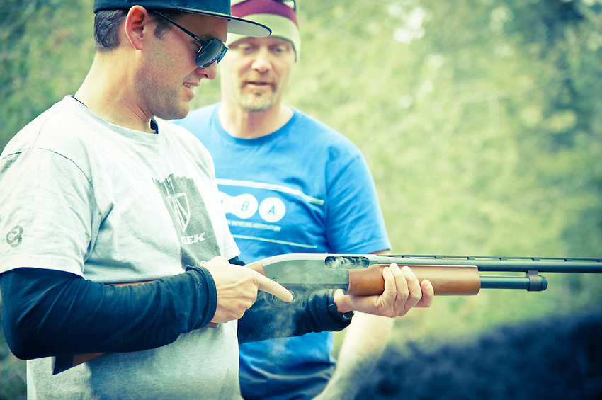 Professional mountain biker Andrew Shandro examines a smoking shotgun while shooting in Copper Harbor Michigan Upper Peninsula.