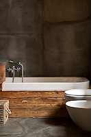 The bathroom has grey stone walls and floor and a contemporary bath surrounded by rustic wooden planks