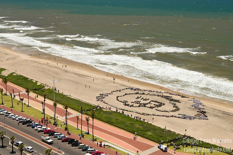 Thousands of South Africa Youth form a giant human lion and call for urgent action on climate change in Durban, South Africa. The event was in partnership with international artist John Quigley, supported by the TckTckTck campaign and Porteon Solar Electric vehicles. Credit: Robert van Waarden / Spectral Q