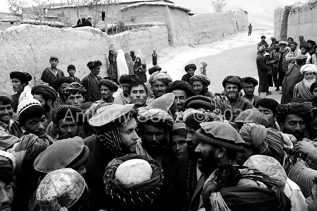 Northern Afghanistan<br /> October 2001<br /> <br /> John (center) is surrounded by a crowd of refugees as he attempts to negotiate a small oil distribution in the heart of the Nowabad camp.