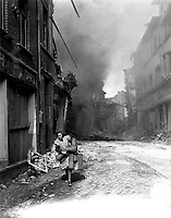 German woman carrying a few possessions runs from burning building in Seigburg, Germany.  Fire started by Nazi saboteur.  April 13, 1945.  T4c. Troy A. Peters, USA. (Roberts Commission)<br /> NARA FILE #:  239-PA-70-4<br /> WAR &amp; CONFLICT BOOK #:  1092