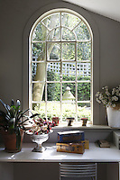A laburnum tree in the garden is framed in the arched window of the garden room