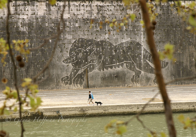 Person walking dog beside Tiber River, Rome, Italy, Europe