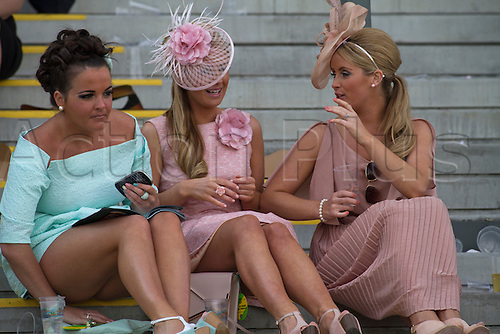 13.04.2012 Aintree, England. The Grand National Festival Ladies Day. Three women racegoers sitting chatting and drinking in one of the grandstands after the final race of the day.