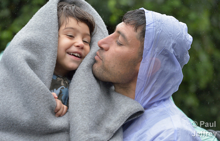 Refugees on their way to western Europe, a man from Iran holds his son as they approach the border into Croatia near the Serbian village of Berkasovo.