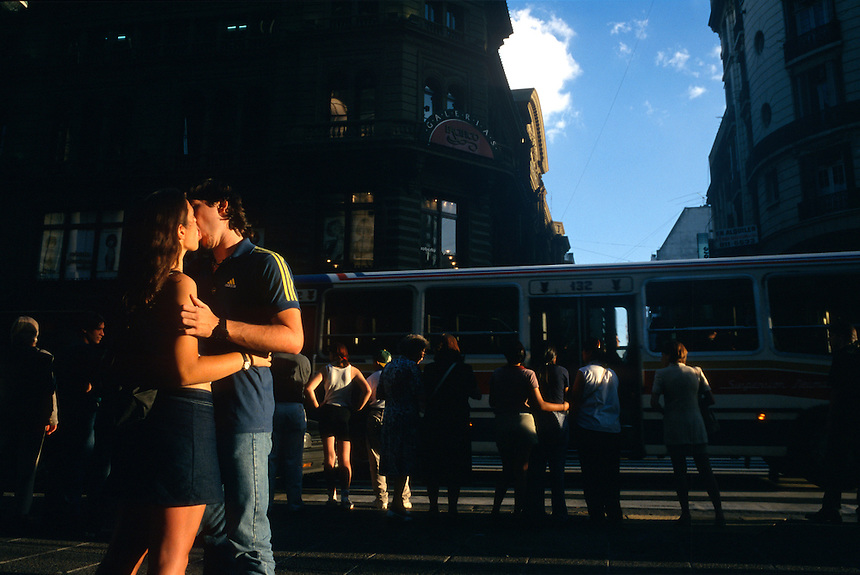 Lovers kiss in the evening light on the downtown Buenos Aires shopping strip of Calle Florida.