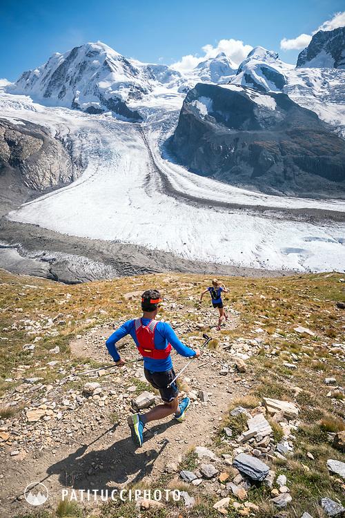 Trail running down a steep trail off the Gornergrat, with Monte Rosa in the background. Zermatt, Switzerland.
