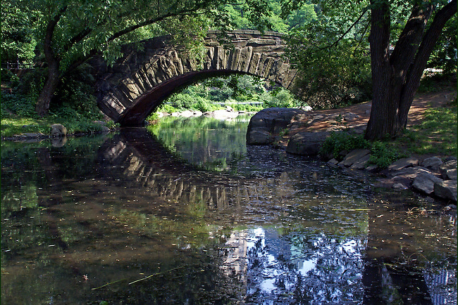 The iconic, stone, Central Park Gapstow Bridge gracefully arches over and is reflected in the narrow neck of the Pond. The bridge, which has been seen in many movies, was built in 1896 and is 12 feet high and 76 feet in length.