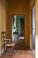 View through open door from yellow hallway into room beyond, Chateau de la Bourlie, Dordogne