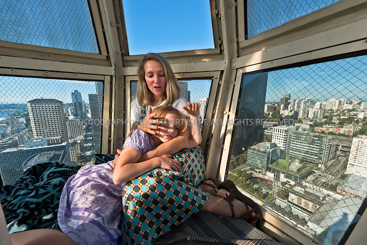 9/27/2010--Seattle,WA, USA..Petra Franklin, 46, and her daughter Simone, 6, in the lighthouse at the very top of her penthouse apartment in Smith Tower Seattle. ..Smith Tower, located in Seattle's Pioneer Square neighborhood, is the oldest skyscraper in the city. Completed in 1914 it has 38 floors and  remained the tallest building on the West Coast until the Seattle Space Needle overtook it in 1962. The tower is 462 ft (143 meters) from street level to the top of the pyramid with a small glass lighthouse at the top...Petra Franklin and her husband David Lahaie live in the pyramid on top of Smith Tower with their two daughters Simone, 6, and Naomi, 3. Franklin is co-founder and general partner of Vault Capital, a venture capital fund with offices in Smith Tower...Copyright © 2010 Stuart Isett. All rights reserved.