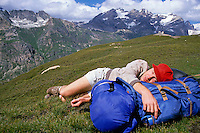 Male hiker taking a nap on top of a mountain, French Alps, France.