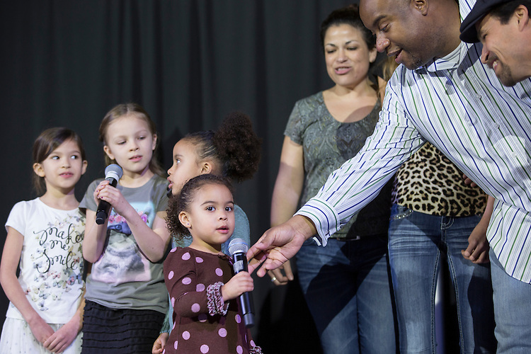 "Assistant Dean of Students Jamie Patton hands the microphone to his 3-year-old daughter Eboni Patton during their performance of ""We are the World"" during the Faculty Pageant on February 22, 2016. Patton took first place at the pageant."