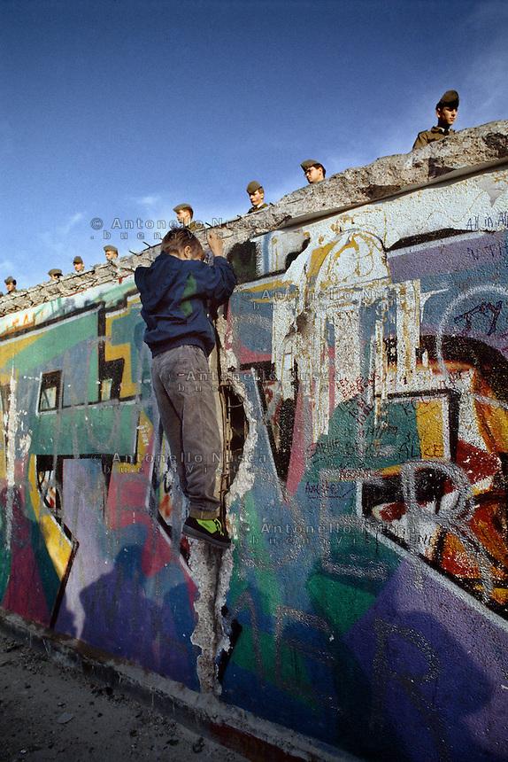 Berlino, 9 Novembre, 1989. Un bambino si arrampica sul muro di Berlino presidiato da soldati della Germania dell'Est poco prima della sua caduta. East German border guards try to prevent a crowd climbing onto the Berlin Wall on the morning that the first section was pulled down.