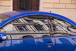 reflection of old building in a modern blue car in rome italy