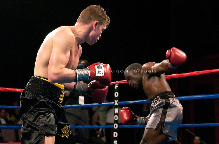 Yuri Foreman (black and yellow trunk) and Charles Clark during their 8 rounds Jr. Middleweight fight at The Foxwoods Casino in Mashantucket, CT on 04.26.03. Foreman won by TKO in the 2nd round