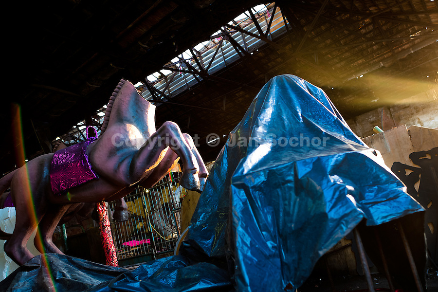 A damaged carnival statue of a horse abandoned in the Samba school warehouse in Rio de Janeiro, Brazil, 14 February 2012. Most of the large carnival floats, colorful designs and fancy costumes are dismantled, cut into pieces or simply thrown into garbage right after the last day of the Carnival. The low-tech materials as fiberglass, plastic or polystyrene, which most of the of the carnival floats and statues are made of, are stocked in the warehouses to be recycled and used in the future parades. However, there is no use for some of the statues so they slowly fall apart into pieces forming a ?Carnival cemetery? in the industrial yards around the port of Rio de Janeiro.