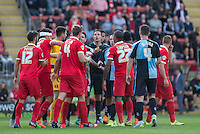 Players confront each other as Referee James Linington controls the situation  during the Sky Bet League 2 match between Leyton Orient and Wycombe Wanderers at the Matchroom Stadium, London, England on 19 September 2015. Photo by Andy Rowland.
