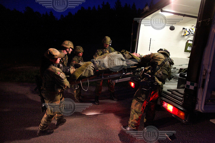 Soldiers find a wounded man in the forest at night, treat him and carry him on a stretcher. Norwegian Home Guard soldiers during exercise Djerv..The Home Guard has traditionally been designated to secure important  domestic installations in case of war or crisis. With the cold war long gone, a war in Afghanistan and budget cuts, there is a debate over the Home Guard's role in the future.
