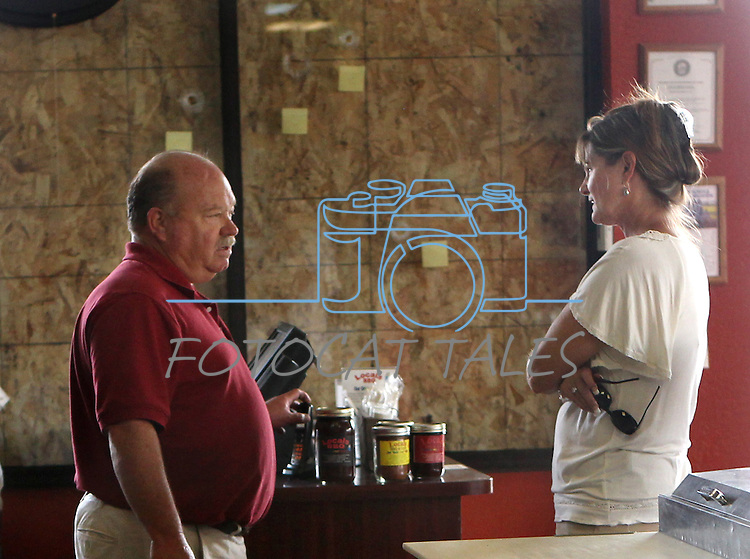 With bullet holes in the boarded up windows behind him, Locals BBQ owner Ralph Swagler talks with Cherie Santillo of the Carson City Health Department in Carson City, Nev. on Wednesday, Sept. 7, 2011. Swagler's business was damaged in Tuesday's IHOP shooting spree that left five dead and seven injured. (AP Photo/Cathleen Allison)