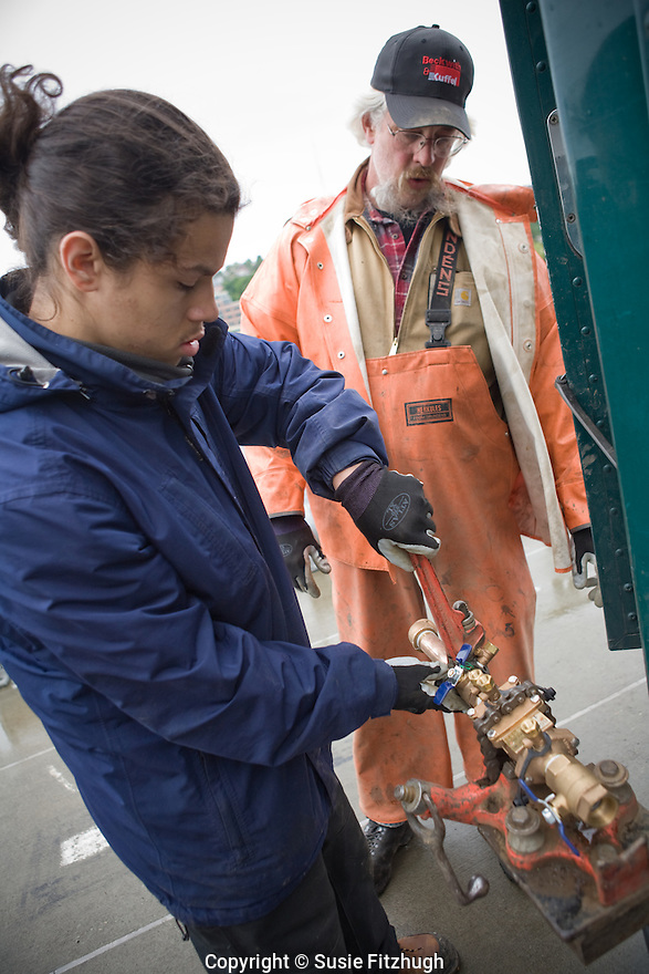 Gino Castro, a student at Rainier Beach HS, works with Dan Dal Pozzo, a plumber with the Seattle Parks and Recreation department, on a job to repair the water supply for the historic steamer Virginia V on Lake Union.