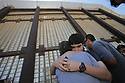 Monica Nieblas hugs her son Eduardo Rivas, 13, as his father, Cain Rivas, behind at right, looks through the border wall at Friendship Park, 04/16/17, in San Diego, California.  photo by Bill Wechter
