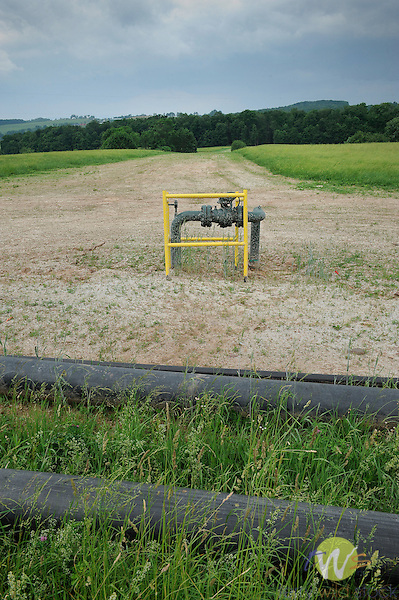 Marcellus shale gas industry. Chief Oil and Gas Company. Lycoming County, Penn Township. Above ground gas control valve with farmland and new pad water lines......................................