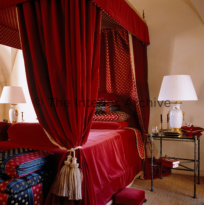Sumptous red velvet drapes with a red and gold lining hang around this four-poster bed