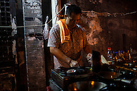 Liu Pang Wa cooks at a nameless shaokao restaurant on the sidewalk near the west gate of the Ciqikou area of Shapingba district in Chongqing, China. Ciqikou's ancient town is a major tourist destination in Chongqing, but at night, the tourists disappear and locals come out to eat from street food vendors in the area.<br /> <br /> The restaurant is run by Liu Pang Wa, whose wife and two children also help. Most of the customers there are neighborhood locals, and the restaurant stays open until 3 or 4 am. Liu Pang Wa said his specialties are eggplant, pig brain, and fish. The area is close to western banks of the Jialing River in northwestern Chongqing city.