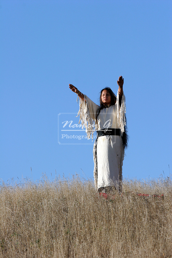 A Native American Indian woman standing with her arms extending to the sun in the prairie of South Dakota