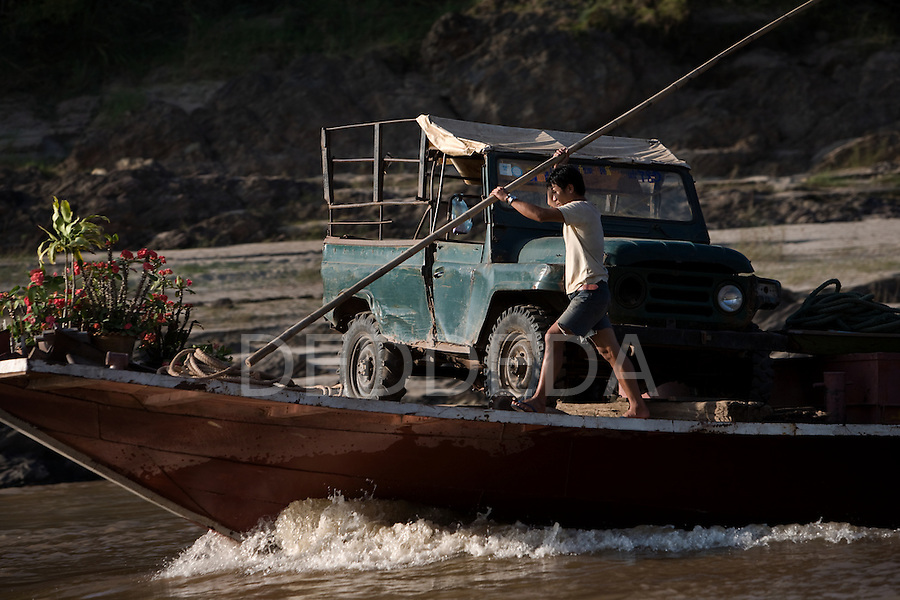 A man transports a jeep on his wooden river boat along the Mekong River in Laos.
