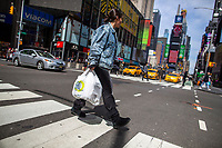 NEW YORK, NY - APRIL 2: A woman carries her shopping  plastic bag as she walks along Times Square on April 2, 2019 in New York. New York will become the second state in U.S. to ban shops from providing single-use plastic bags for most purchases.   (Photo by Eduardo MunozAlvarez/VIEWpress)