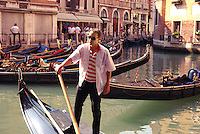Gondolier on his gondola closeup in Venice canal